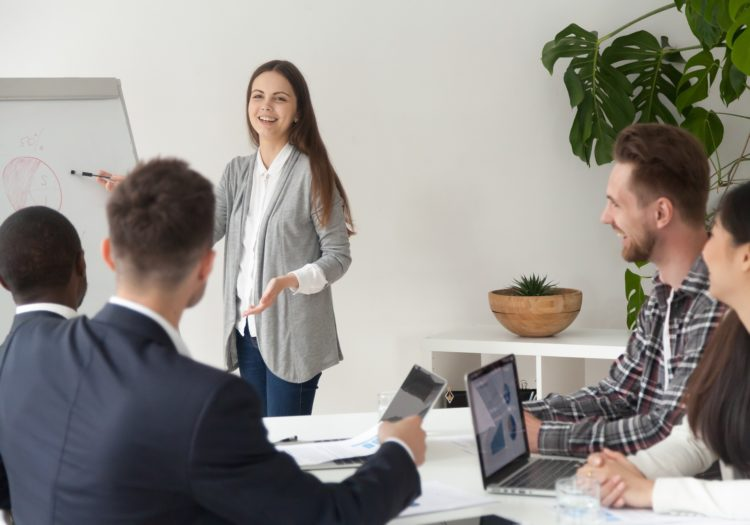 Smiling young employee or manager giving presentation working on flipchart in meeting room making business offer or reporting about project results, explaining new plan or idea to multi-ethnic team